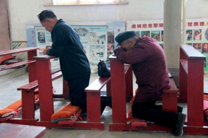 Dos hombres rezan en una iglesia católica de China. AYUDA A LA IGLESIA NECESITADA.
